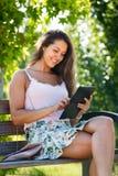 Muchacha en banco en parque con el ereader Imágenes de archivo libres de regalías