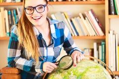 Muchacha en biblioteca con el globo y la lupa Imagen de archivo