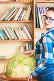 Muchacha en biblioteca que señala al globo Imagen de archivo libre de regalías