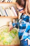 Muchacha en biblioteca que señala al globo Fotos de archivo
