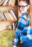 Muchacha en biblioteca que señala al globo Imagen de archivo