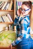 Muchacha en biblioteca que señala al globo Fotografía de archivo