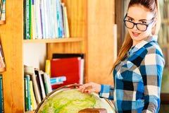 Muchacha en biblioteca que señala al globo Foto de archivo