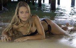 Muchacha en bikini debajo de un embarcadero Imágenes de archivo libres de regalías