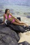 Muchacha en bikini en rocas de la lava Imagenes de archivo