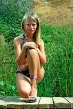 Muchacha en bikini en un embarcadero de madera Imagen de archivo