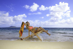 Muchacha en bikini en una silla de playa Foto de archivo libre de regalías