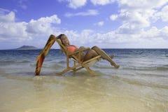 Muchacha en bikini en una silla de playa Imagenes de archivo
