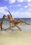 Muchacha en bikini en una silla de playa Imágenes de archivo libres de regalías