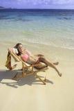 Muchacha en bikini en una silla de playa Fotografía de archivo libre de regalías