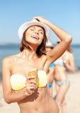 Muchacha en bikini que come el helado en la playa Imagen de archivo
