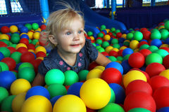 Muchacha en bolas coloridas Imagenes de archivo