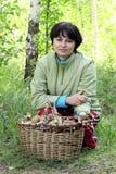 Muchacha en bosque al lado de una cesta de setas Fotos de archivo libres de regalías