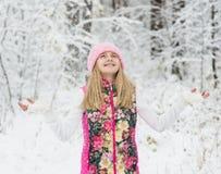 Muchacha en bosque del invierno que disfruta de las nevadas Imagenes de archivo