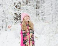 Muchacha en bosque del invierno que disfruta de las nevadas Imagen de archivo