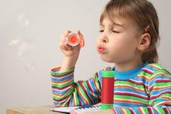 Muchacha en burbujas de jabón de la camisa que soplan multicolora fotografía de archivo