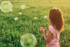 Muchacha en burbujas de jabón del vestido que soplan rosado en verano Imagen de archivo