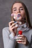 Muchacha en burbujas que soplan del cuello alto Cierre para arriba Fondo gris Imagen de archivo
