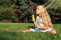 Muchacha en burbujas que soplan del parque Fotos de archivo libres de regalías