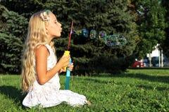 Muchacha en burbujas que soplan del parque Imagen de archivo