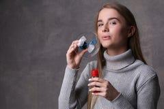 Muchacha en burbujas que soplan del suéter Cierre para arriba Fondo gris Fotografía de archivo