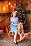 Muchacha en caballo de madera del juguete cerca del árbol de navidad Imagenes de archivo