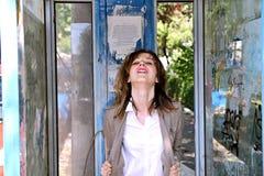 Muchacha en cabina del teléfono Foto de archivo libre de regalías
