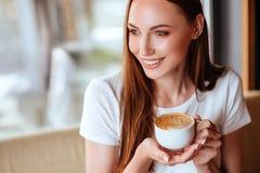 Muchacha en café con capuccino fotos de archivo