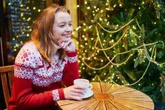 Muchacha en café de consumición del suéter del día de fiesta o chocolate caliente en el café adornado para la Navidad imagen de archivo