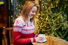 Muchacha en café de consumición del suéter del día de fiesta o chocolate caliente en el café adornado para la Navidad foto de archivo