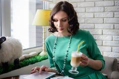 Muchacha en café de consumición del vestido verde Imagen de archivo