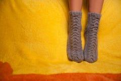 Muchacha en calcetines hechos punto en el sofá Imagen de archivo