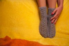Muchacha en calcetines hechos punto en el sofá Fotos de archivo libres de regalías