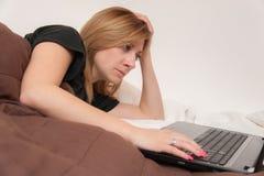 Muchacha en cama con el ordenador portátil Foto de archivo