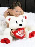 Muchacha en cama con un oso de peluche Foto de archivo libre de regalías