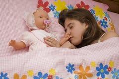 Muchacha en cama con una muñeca Fotos de archivo libres de regalías