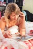 Muchacha en cama que habla en el teléfono mientras que lee imagen de archivo libre de regalías