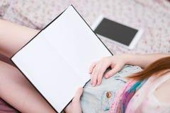 Muchacha en cama que lee un libro Fotografía de archivo libre de regalías