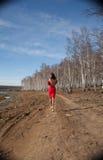 Muchacha en caminar rojo del vestido Imagenes de archivo