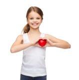 Muchacha en camisa blanca en blanco con el pequeño corazón rojo Foto de archivo