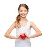 Muchacha en camisa blanca en blanco con el pequeño corazón rojo Foto de archivo libre de regalías