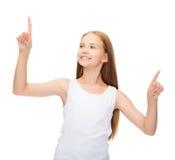 Muchacha en camisa blanca en blanco que señala algo Fotografía de archivo libre de regalías