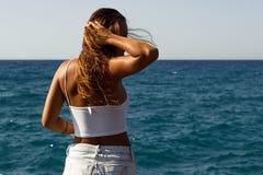 Muchacha en camisa corta en la playa que juega con el pelo Fotos de archivo libres de regalías