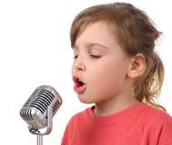 Muchacha en camisa que canta en el micrófono, media carrocería imagen de archivo