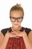 Muchacha en camisa roja con las manos dobladas y los vidrios de moda negros Imagen de archivo libre de regalías