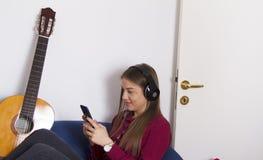 muchacha en camisa roja Se considera móvil y escucha la música imagen de archivo libre de regalías