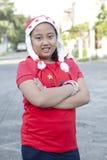 Muchacha en camisa roja y el sombrero de santa que se colocan en la calle del pueblo Foto de archivo libre de regalías