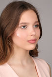 Muchacha en camisa rosada con crema en su cara Cierre para arriba Fondo gris Fotos de archivo libres de regalías