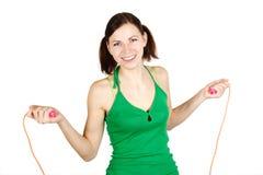 Muchacha en camisa verde con la cuerda que salta, sonriendo Imagenes de archivo