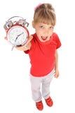 Muchacha en camiseta y reloj de alarma rojos. Fotografía de archivo